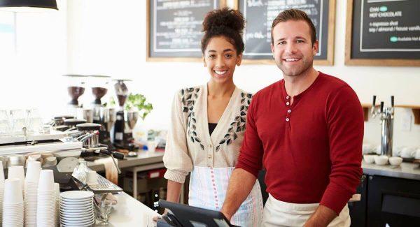 Commerçants souriant derrière leur caisse enregistreuse