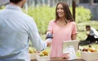 Commerçant présentant un lecteur de carte mobile