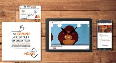 Carte bancaire Compte Nickel avec un prospectus et l'appli Compte Nickel sur un smartphone