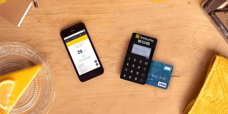 Pocket Smile de Smile and Pay à droite et smartphone à gauche posés sur une table