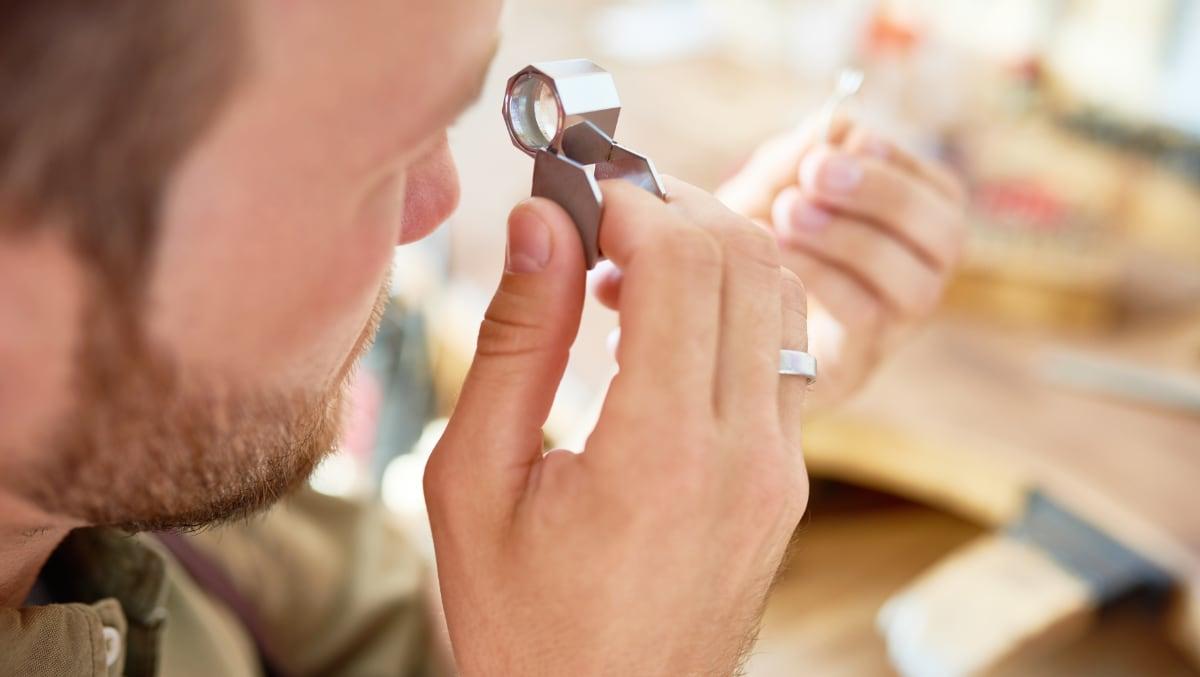 Homme examinant un bijou à la loupe
