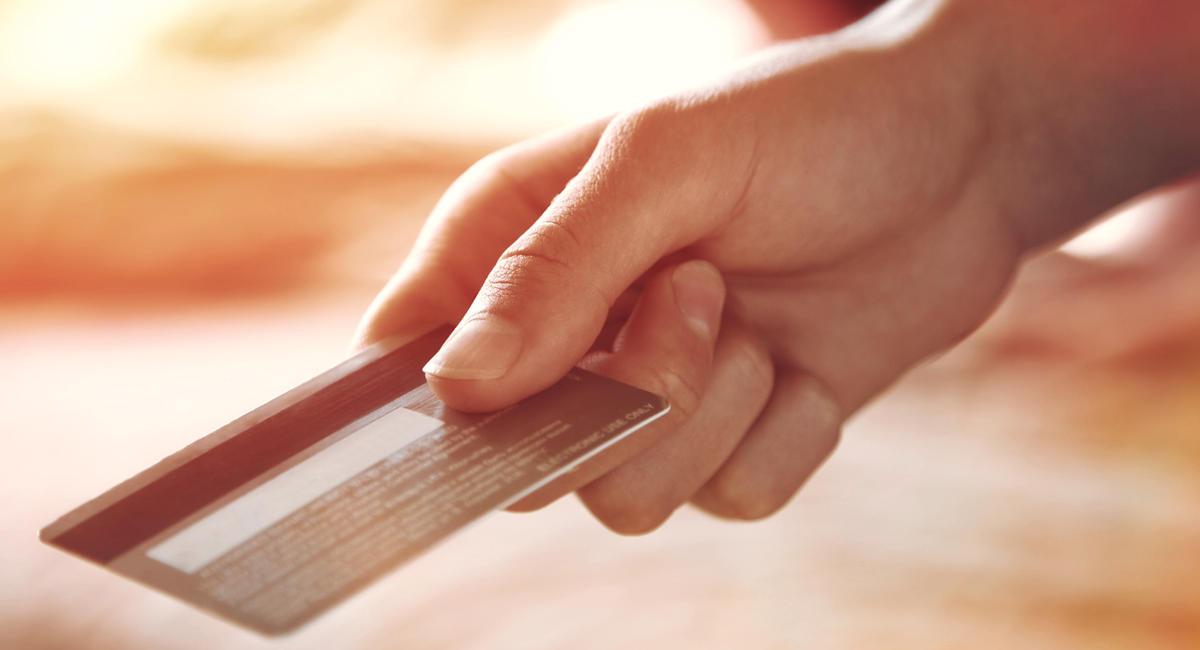Main tendant une carte bancaire