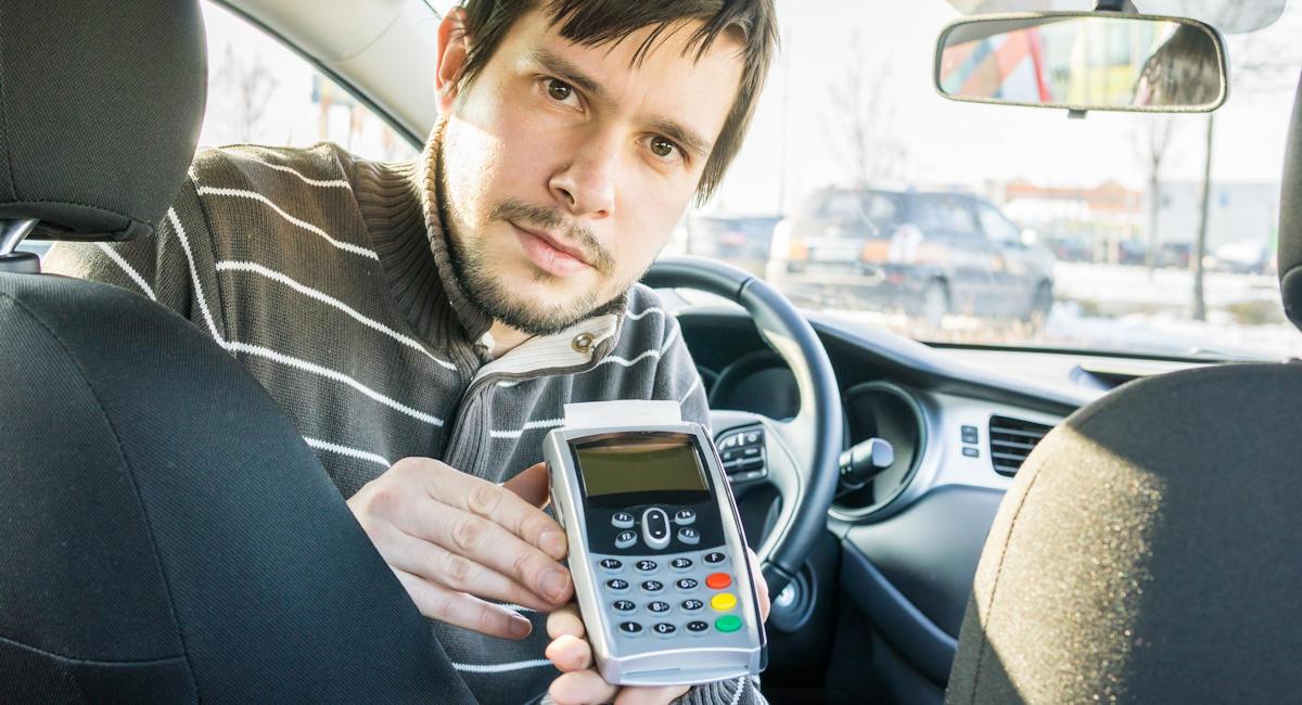 Chauffeur de taxi ou VTC présentant un terminal de paiement