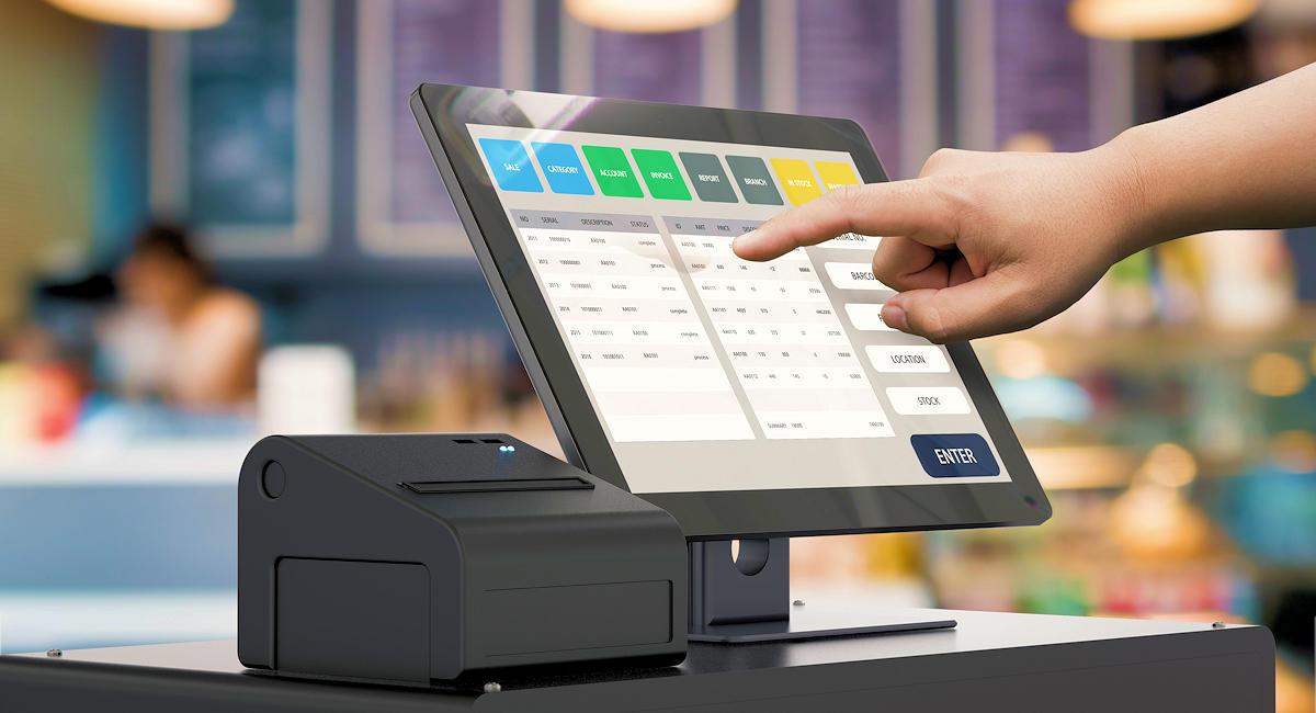 Doigt appuyant sur l'écran d'une caisse tactile