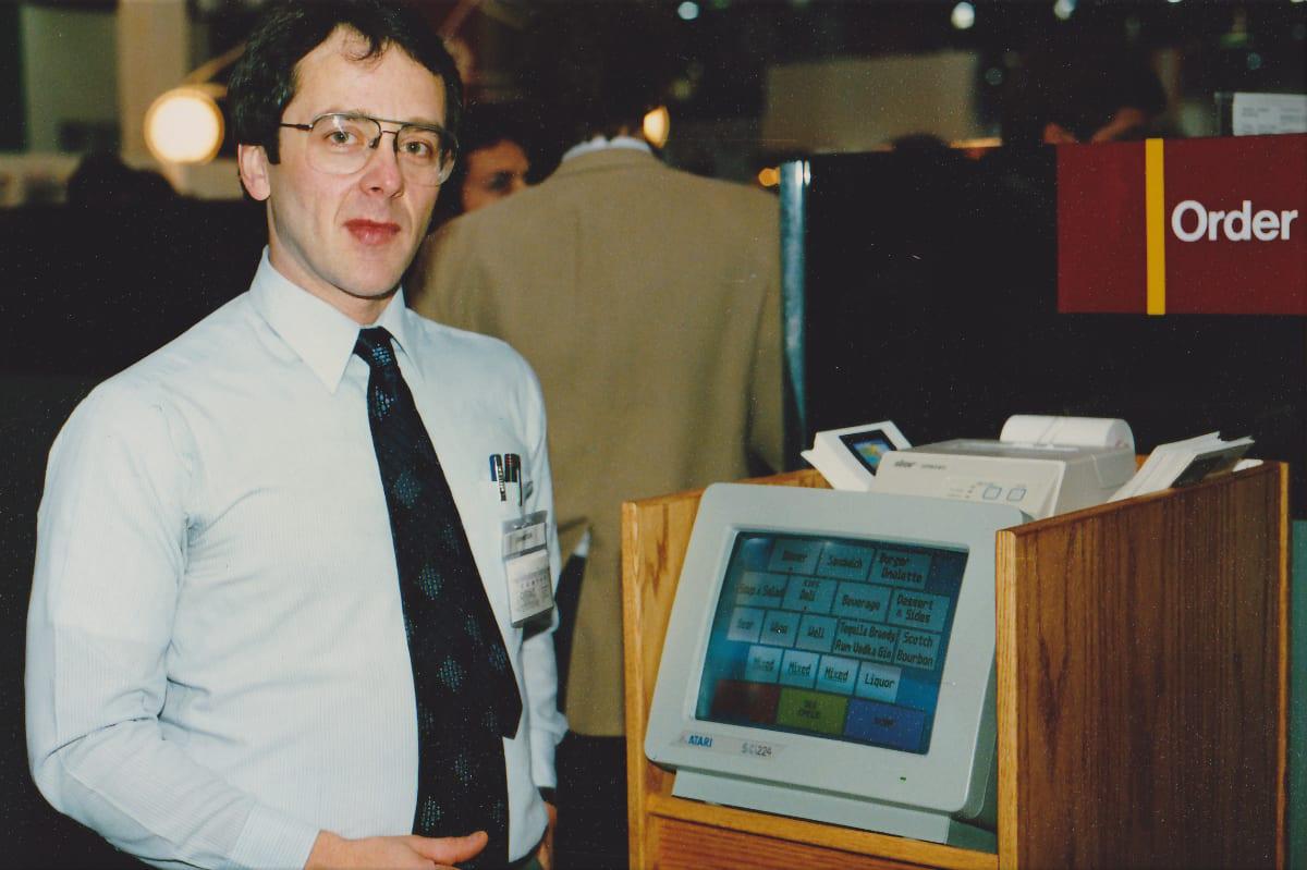 Gene Mosher devant sa caisse à écran tactile